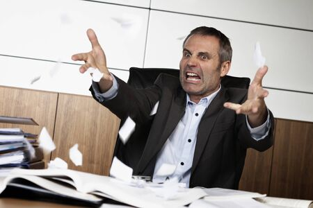 Frustrated office manager tearing document.