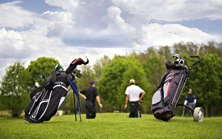 Deux sacs de golf debout devant un groupe de joueurs de golf putting on green.