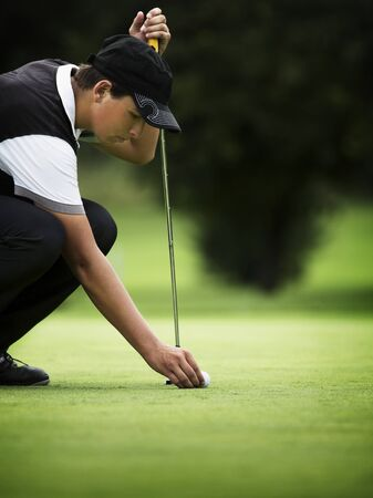 Male golfer squating at green.