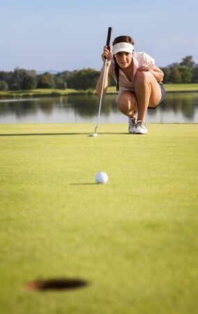 Girl golfer analyzing the green for putting the ball into cup.