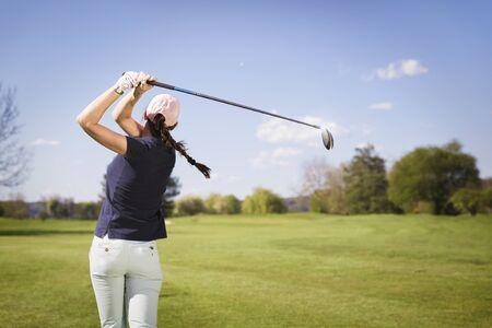 Vrouwelijke golfspeler swingende golfclub.
