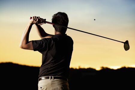 Close up professional golf player in black shirt teeing off ball in twilight, view from behind.