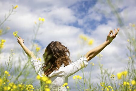 Young woman standing in yellow rapeseed field raising her arms expressing gratitude or freedom, view from behind.
