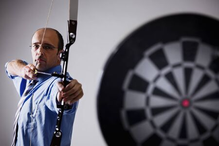 Business person aiming at target.