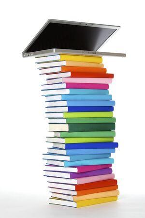 Concetto di e-learning: laptop in cima alla pila di libri veri colorati su sfondo bianco, vista laterale.