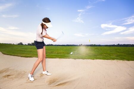 Girl golf player chipping ball in bunker.