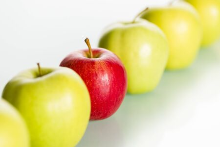Red apple standing out from row of green apples. Stock Photo