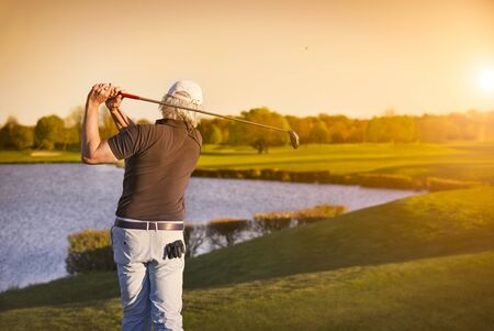 Golf player teeing off at sunset. Stock fotó