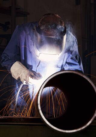 Worker welding pipe in workshop. Stockfoto