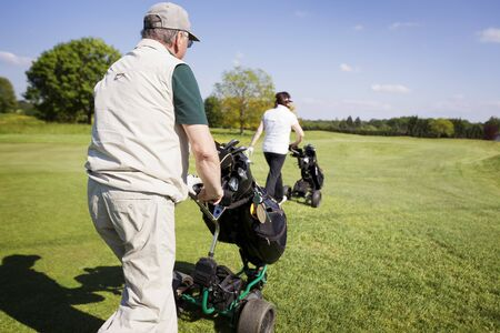Gold couple walking on fairway with bags. Stock Photo