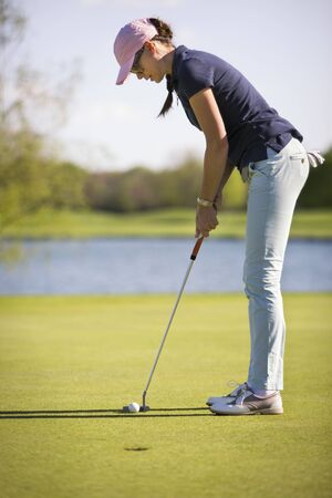 Female golf player putting on green.