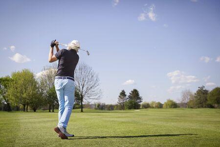 Stary golfista strzelanie na zielono.