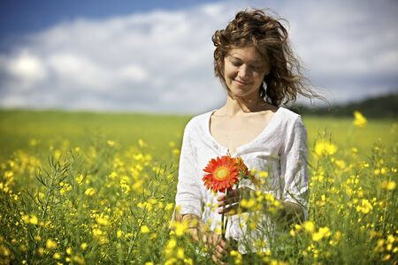 Woman with red flowers in rapeseed field. Archivio Fotografico