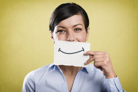 Smiling businesswoman holding blank white card in front of her mouth.