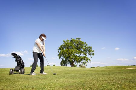 Woman focusing on golf fairway.