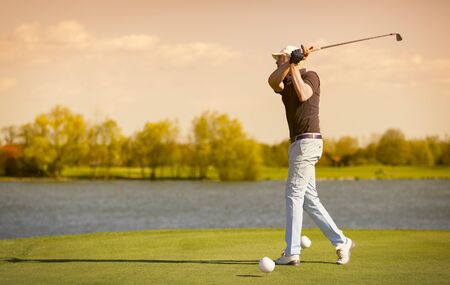 Elder golf player teeing off. 免版税图像