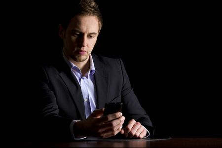 Business executive checking text messages on phone. 免版税图像