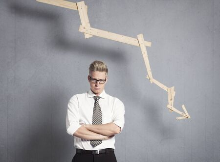 Displeased businessman in front of graph with negative trend.