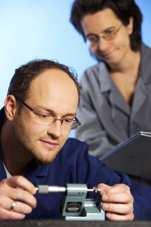 Macro of engineer measuring with assistant
