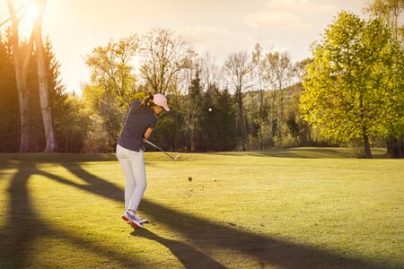 Female golf player at sunset.