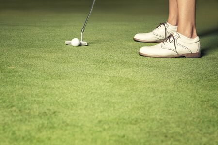 Close up of woman about to make a putt. Foto de archivo