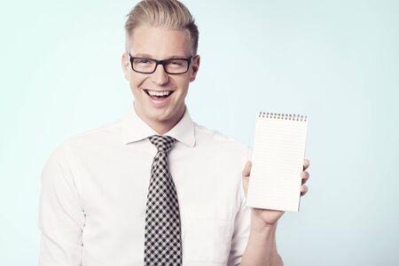 Joyous businessman presenting blank notepad.