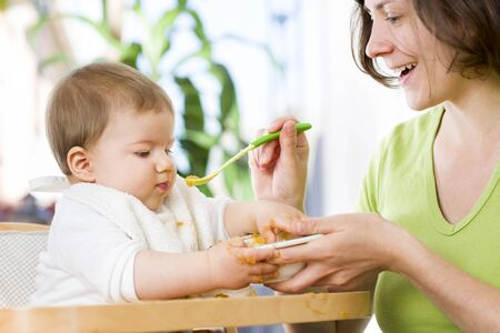 Lovely baby boy playing with food while eating.