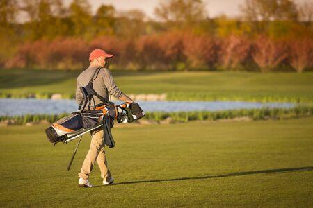 Golfer walking on faiway.