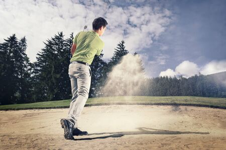 Young golfer in sand trap.