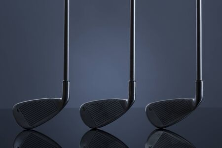 Golf clubs standing on reflective surface, isolated on dark blue background. Stok Fotoğraf