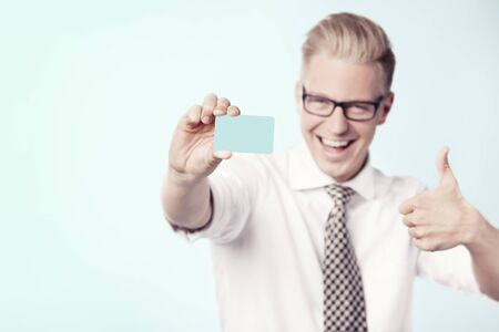 Laughing businessman giving thumbs up at blank card. Stock Photo