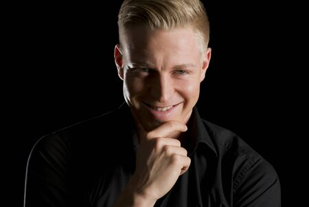Low key portrait of smiling seductive man looking straight.