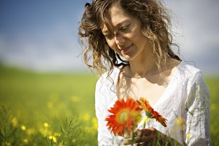 Woman holding red flowers in field.