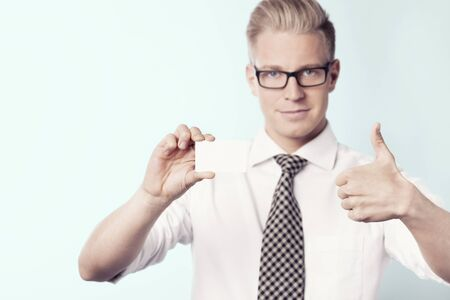 Friendly businessman giving thumbs up at white empty card.