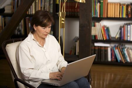 Attractive senior woman sitting and working on laptop