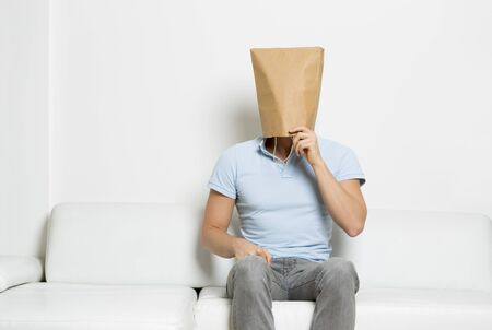 Thinking man with face covered sitting on couch.