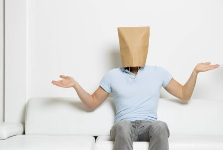 Confused man with paper bag covering his head.