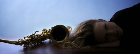 Woman lying next to saxophone