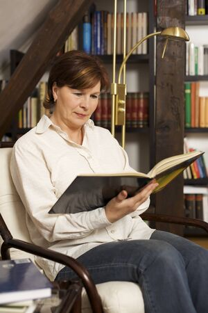 Pretty senior woman sitting and reading a book Stock Photo