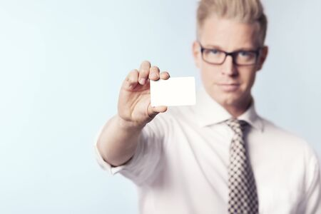 Likable businessman showing white blank card. Imagens