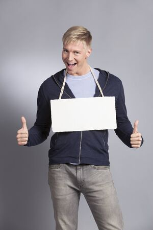 Excellent news: Overjoyed man giving thumbs up at white empty signboard with space for text isolated on grey background.