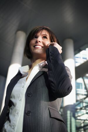 Young confident female professional talking on mobile phone in front of office building Stockfoto