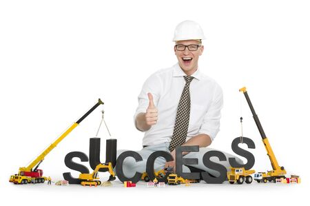 Working on success concept: Overjoyed businessman giving thumbs up along with construction machines building the word success, isolated on white background.