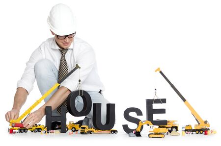 House under construction concept: Smiling engineer building the word house along with construction machines, isolated on white background. Stockfoto
