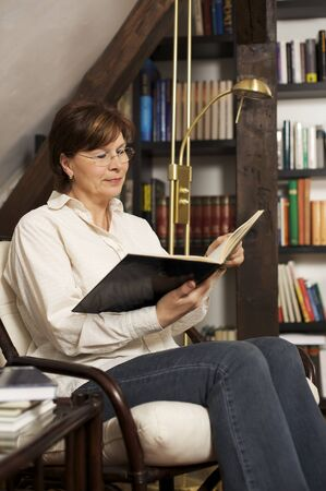 Smiling senior woman sitting and reading a book Stock Photo