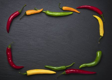 Slate framed by colorful chili peppers. Imagens - 131593499