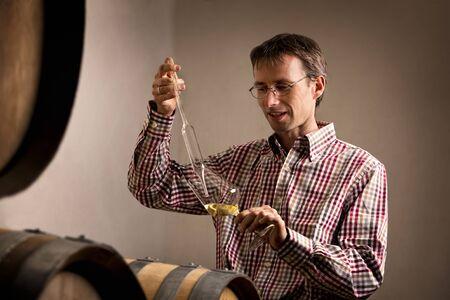 Vintner taking sample of white wine in cellar.