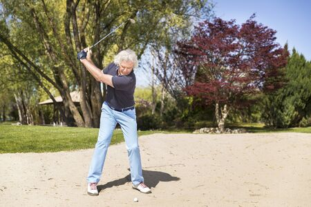 Senior golf player swinging golf club in sand bunker. Stockfoto