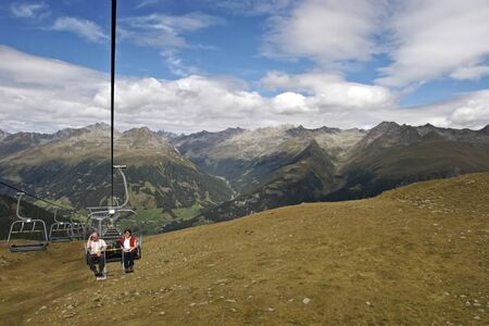 Two senior hiker sitting on chair lift going uphill with beautiful mountain panorama of Lienzer Dolomites in Tyrol, Austria.