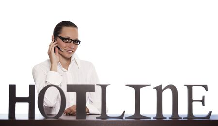 Smiling female phone operator in call centre sitting at desk and talking with headset providing customer support, isolated on white background. Stockfoto